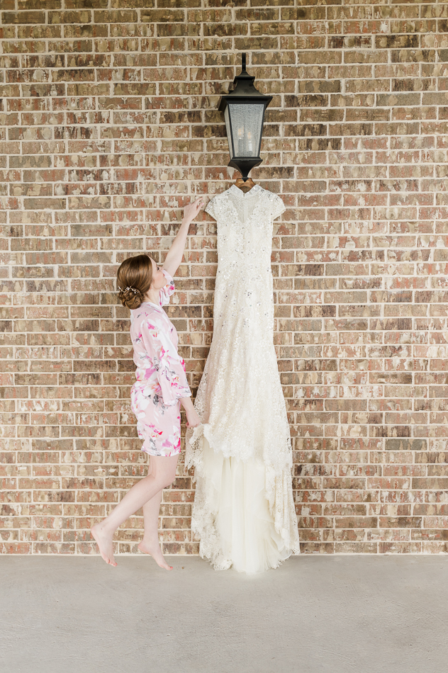 Bride in robe looking at her wedding dress, dallas wedding photographer