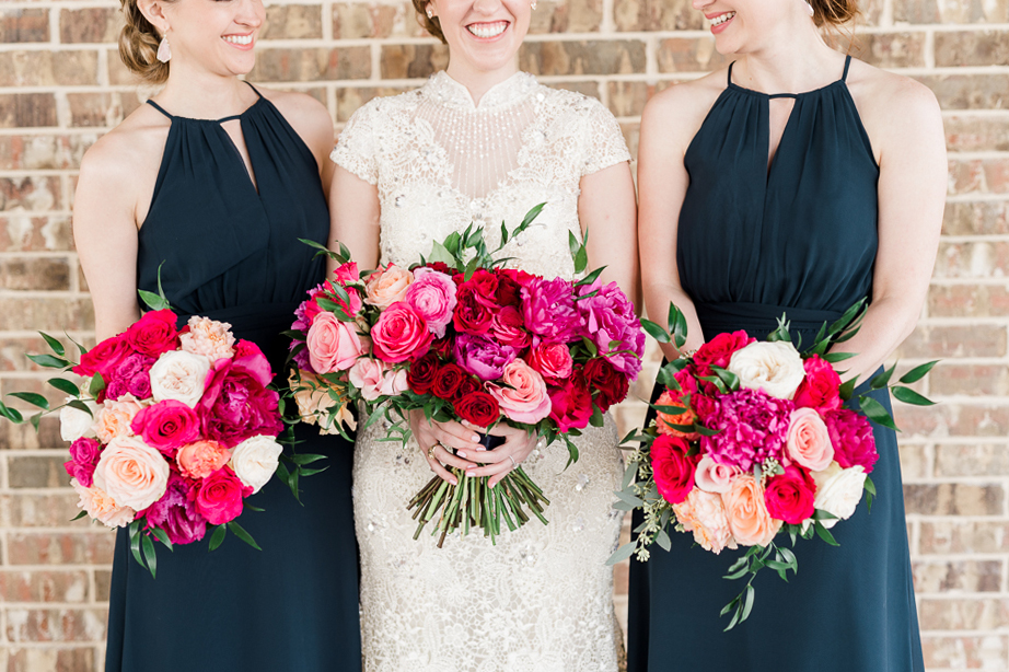 bridesmaids with pink bouquets and wearing navy dresses